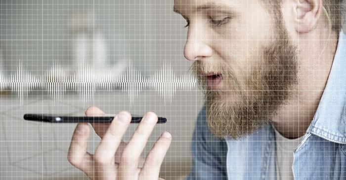 Man som spelar in ljudet av sin hostning på en smartphone.
